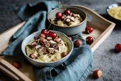 小米粥冠上了与巧克力片、榛子、杏仁切片和樱桃 免版税库存图片