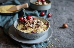 小米粥冠上了与巧克力片、榛子、杏仁切片和樱桃 图库摄影