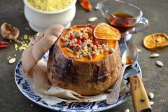 小米粥在一个南瓜烘烤了,用莓果、蜂蜜和坚果 免版税库存图片
