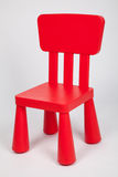 小红色塑料儿童` s椅子 库存照片