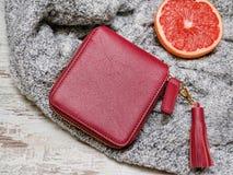 小红色妇女的钱包、毛线衣和柑橘在木背景 秀丽蓝色聪慧的概念表面方式构成妇女 库存照片