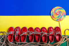 小红色小船在背景的大多彩多姿的棒棒糖附近穿上鞋子 顶视图,拷贝空间 框架 小组孩子 免版税库存照片