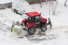 小红色拖拉机雪犁在降雪期间的庭院里 免版税库存照片