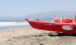小红色救生员船在海旁边停放 免版税库存图片