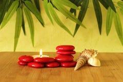 小红色石头在禅宗生活方式的专栏与一个蜡烛和在竹木地板和绿色叶子backgr上的海滩壳安排了 库存图片