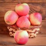 小红色苹果在一张木桌上和在篮子 背景棕色木 苹果照片 健康自然点心 免版税库存照片