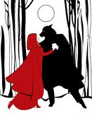 小红骑兜帽和狼跳舞在根据满月的森林里 免版税图库摄影