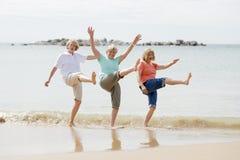 小组三资深成熟他们的60s的退休的妇女获得乐趣一起享受愉快走在海滩微笑的嬉戏 免版税库存图片