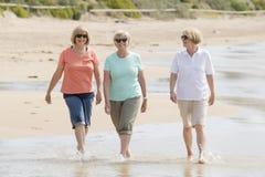 小组三资深成熟他们的60s的退休的妇女获得乐趣一起享受愉快走在海滩微笑的嬉戏 库存照片