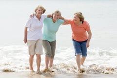 小组三资深成熟他们的60s的退休的妇女获得乐趣一起享受愉快走在海滩微笑的嬉戏 图库摄影