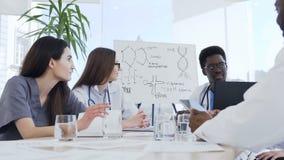 小组不同种族有膝上型计算机的专业医生在见面在医疗办公室 健康,医院,行业 股票录像