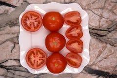 小组与厨刀的新鲜的成熟整个和被切的蕃茄葡萄酒黑色表面上 顶视图点 库存照片