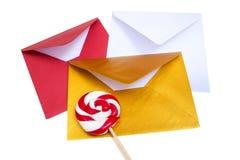 小组与红色和白色棒棒糖的开放多彩多姿的信封 图库摄影