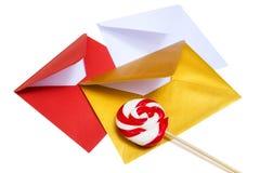 小组与红色和白色棒棒糖的开放多彩多姿的信封 库存照片