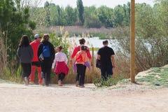 小组两个家庭在湖的一星期六下午,读了 免版税库存图片