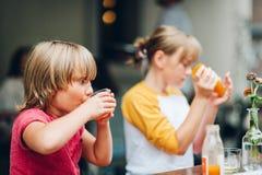 小组两个滑稽的孩子有饮料在咖啡馆 免版税库存图片