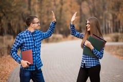 小组两名年轻欣快学生愉快的通过的检查用步行的手在公园 库存图片