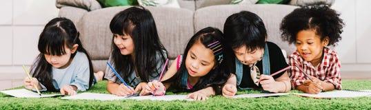 小组五个不同种族的年轻逗人喜爱的学龄前孩子、男孩和女孩愉快的研究或者图画一起在家或学校 免版税库存照片