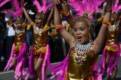 小组五颜六色的椰子服装的女孩参加了街道跳舞 库存照片