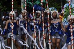 小组五颜六色的椰子服装的女性参加了街道跳舞 免版税库存照片