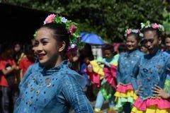 小组五颜六色的椰子服装的女性参加了街道跳舞 免版税库存图片