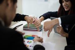 小组亚洲商人显示反感或不同于拇指下来h 免版税库存图片