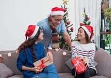 小组亚洲朋友坐沙发庆祝圣诞节和ne 免版税库存照片