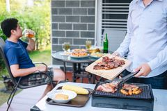 小组享用烤肉的朋友两年轻人和培养一杯啤酒庆祝假日节日愉快饮用 免版税库存图片