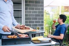 小组享用烤肉的朋友两年轻人和培养一杯啤酒庆祝假日节日愉快饮用 库存图片