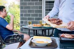 小组享用烤肉的朋友两年轻人和培养一杯啤酒庆祝假日节日愉快饮用 库存照片