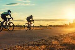 小组人骑自行车在与光束的日落 免版税库存照片