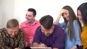 小组会议的青年人在现代顶楼公寓 工作在他们的家庭作业的四名学生使用片剂 影视素材