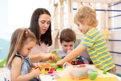 小组使用与彩色塑泥或面团的幼儿园孩子 小孩获得乐趣与五颜六色塑造一起 库存照片