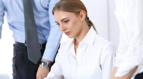 小组使用手提电脑的商人,当谈论成交或群策群力在办公室时 会议和配合 免版税图库摄影