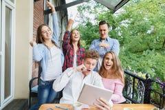 小组使用片剂的十几岁在咖啡馆背景 有片剂的愉快的朋友 享用生活方式现代相当白人妇女的概念长沙发 库存图片