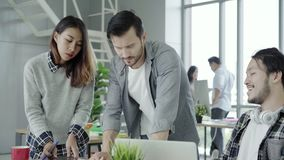 小组便服商人谈论想法在研究膝上型计算机的聪明的便衣,当坐书桌时 影视素材