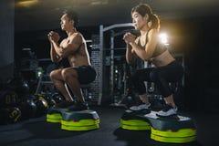 小组健身房的健康健身人民,年轻夫妇解决在健身房,可爱的妇女,并且英俊的肌肉人是trainin 免版税库存图片
