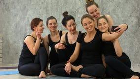 小组健身类的女孩在breaktaking的selfie通过手机,愉快和微笑,显示滑稽的面孔 免版税图库摄影