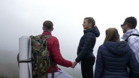 小组到达山顶山的学生探险家顶面敬佩有薄雾的风景谷在一多云有雾的天- 股票视频