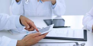 小组医生在医疗会议上 关闭使用触摸板或片剂计算机的医师 库存照片