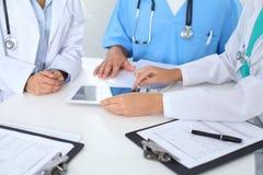 小组医生在医疗会议上 关闭使用触摸板或片剂计算机的医师 免版税图库摄影