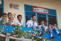 小组印度尼西亚十几岁坐学校` s阳台 免版税图库摄影