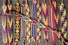 小组友谊简单的手工制造自创自然被编织的镯子在木背景,彩虹颜色,方格的样式的 库存照片
