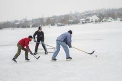 小组另外年迈的人使用hokey在一条冻河的周末 免版税库存图片