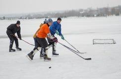 小组另外年迈的人使用hokey在一条冻河Dnipro在乌克兰 库存照片