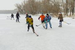 小组另外年迈的人使用hokey在一条冻河Dnipro在乌克兰 免版税图库摄影