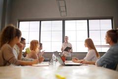 小组可爱的企业家在会议与明亮的窗口和凌乱的会议桌 库存图片