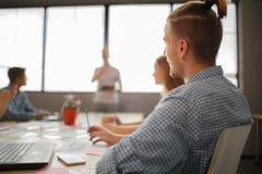小组可爱的企业家在会议与明亮的窗口和凌乱的会议桌 免版税库存照片