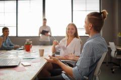 小组可爱的企业家在会议与明亮的窗口和凌乱的会议桌 免版税图库摄影
