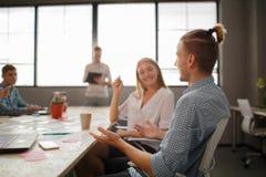 小组可爱的企业家在会议与明亮的窗口和凌乱的会议桌 免版税库存图片